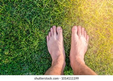 Man feet stand on green grass background