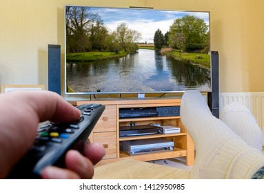 Man with feet up using remote to change tv channels