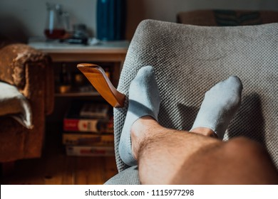Man feet with white socks on chair, first persona perspective, man resting after work