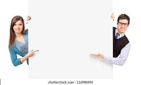 Man and female posing behind a blank panel isolated on white background