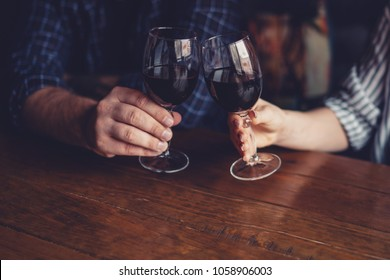 Man and female toasting with glasses of red wine in the restoran. Wine in a glass, selective focus, motion blur. Red wine in a glass. Sommelier pouring the wine into the glass. Thanksgiving Day.