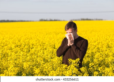 man in field blowing his nose and suffering from hay fever.