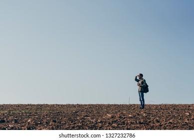 Man in the field looks through binoculars