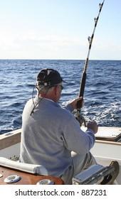 Man in Fighting Chair Reeling in Gamefish