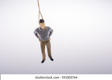 Man  figurine tied  with aa rope on a brown backgorund