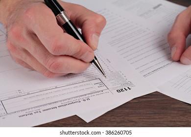 Man filing tax form 1120. United States of America I Corporate Tax Return.
