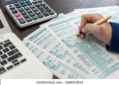 Man fillilng and accounting finance document tax form 1040 with calcualtor. Time for tax