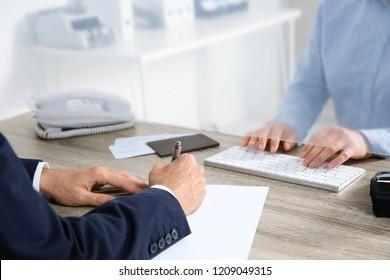 Man filling blank at cash department window, closeup