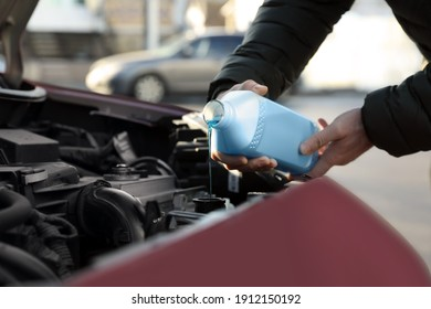 Man filling car radiator with antifreeze outdoors, closeup