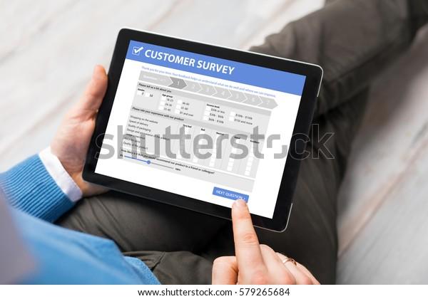 Man filling customer survey form on tablet computer