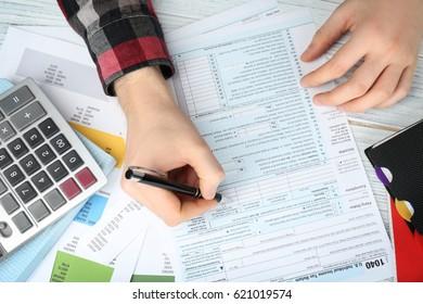 Man filling form of Individual Income Tax Return, closeup