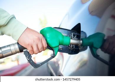 Man filling gasoline fuel in car holding pump. Closeup on male hand refuel car
