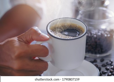 Man filling mug with hot fresh coffee in a morning at home. Close up shot