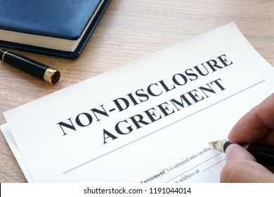 Man is filling in Non-Disclosure Agreement NDA.
