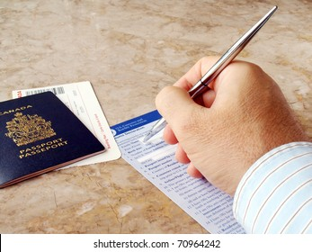 Man filling out U.S. customs and border form with Canadian Passport