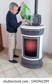 man filling a pellet stove