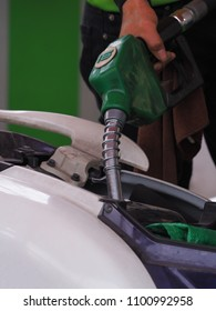 Man filling petrol into a motercycle