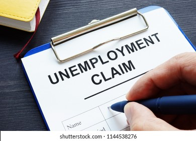 Man is filling in Unemployment claim form.