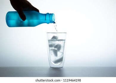 Man filling water from the blue plastic bottle into double glass.  Lighting set up shot on white background.  Concept of good health and refreshment.