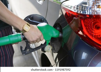 Man fills petrol into her car at a gas station closeup. Man hand holding a fuel pump at a station.
