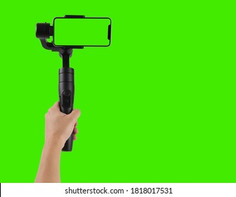 Man filming with a blank screen smartphone using a gimbal stabilizer, isolated on green background chroma key.