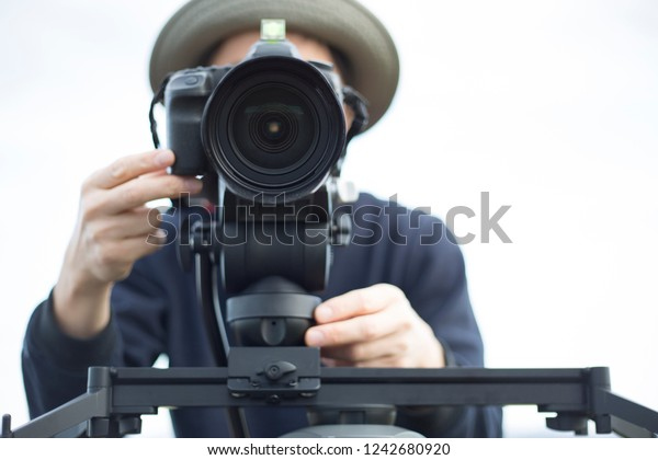 man filming with DSLR