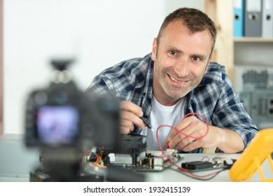 Mann, der sich mit einem Multimeter filmt