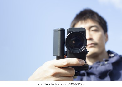 man filming with super 8