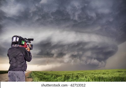 Man filming a supercell thunderstorm in a Kansas field on May 27 2007.