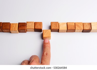 Man finger put last cube wood block to complete and finish wood block in line, symbolizing joining team or making unity teamwork, successful, or completion.