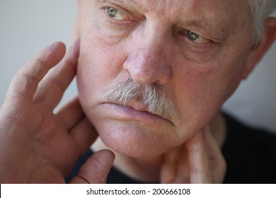 Man with fingers on painful jaw