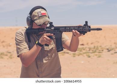 Man firing black rifle on desert range medium 3/4