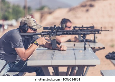Man firing black rifle on desert range bench rest with bipod