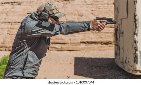 Man firing pistol on desert range medium shot