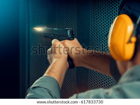 man firing pistol at