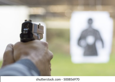 Man Firing Pistol at Target in Shooting Range