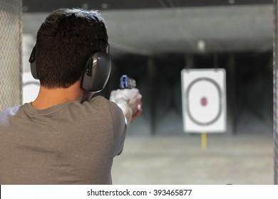 man firing usp pistol at target in indoor shooting range