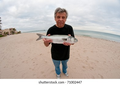 Man with a fish on a sandy beach - through a fish-eye lens
