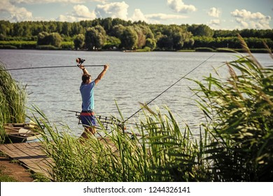 Man fish with spinning tackle on wooden pier. Fisherman cast fishing rod in lake or river water. Adventure, sport, activity. Spin fishing, angling, catching fish. Hobby, vacation, pastime.