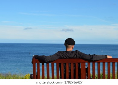 Man in fisherman hat looking out over at the seaside town and coastline during lockdown holiday in Britain. Staycation. Man sat on bench relaxing in the sun.