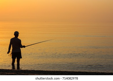 Man Fishing Alone in the Sea at Sunrise (or Sunset)