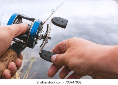 A man is fishing with a baitcasting reel. Hands, a rod and a baitcasting reel