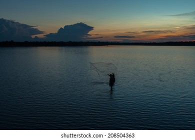 Man fishing from a boat at sunset