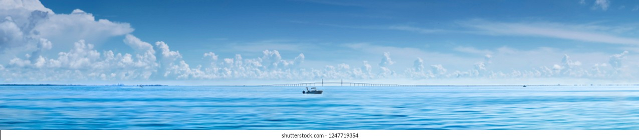 Man fishing from boat with Sunshine Skyway Bridge,Florida in Background