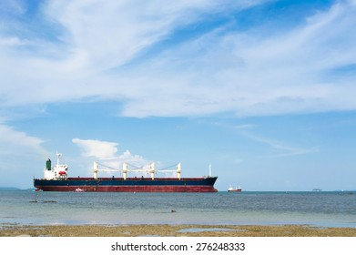 Man fishing infront of Cargo ship on the blue sea under white cloud sky