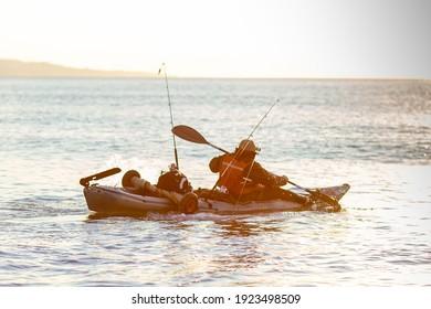 Man fishing in a kayak in the sea. Fisherman kayaking in the Mediterranean sea