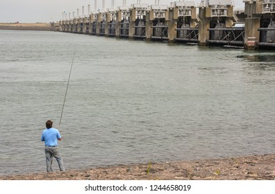 Man fishing next to the Great Dike of Oosterschelde, Holland