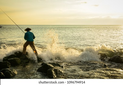 A man fishing on beach at sunset in Lombok Island, Indonesia.
