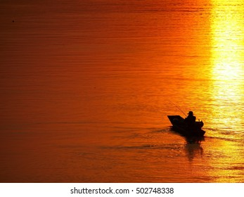 Man fishing on a boat at sunset time