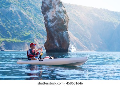 A man fishing on a kayak boat in the sea near the rocks at the shore of island mountain. Young fisherman kayaking.